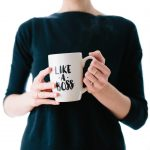 Color image of a female executive holding a coffee mug with the words 'like a boss' printed on the front.