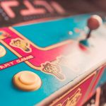 Closeup, color image of mrs. Pacman arcade cabinet joysticks and graphics of mrs. pac-man. Vivid pink and teal colors.
