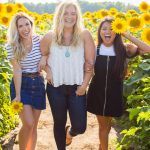 Three young women laughing in a field of sunflowers.