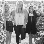Black and white image of three young women laughing in a field of sunflowers.