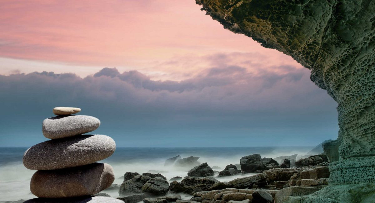A stack of balanced rocks standing on a rocky, windswept shoreline. with
