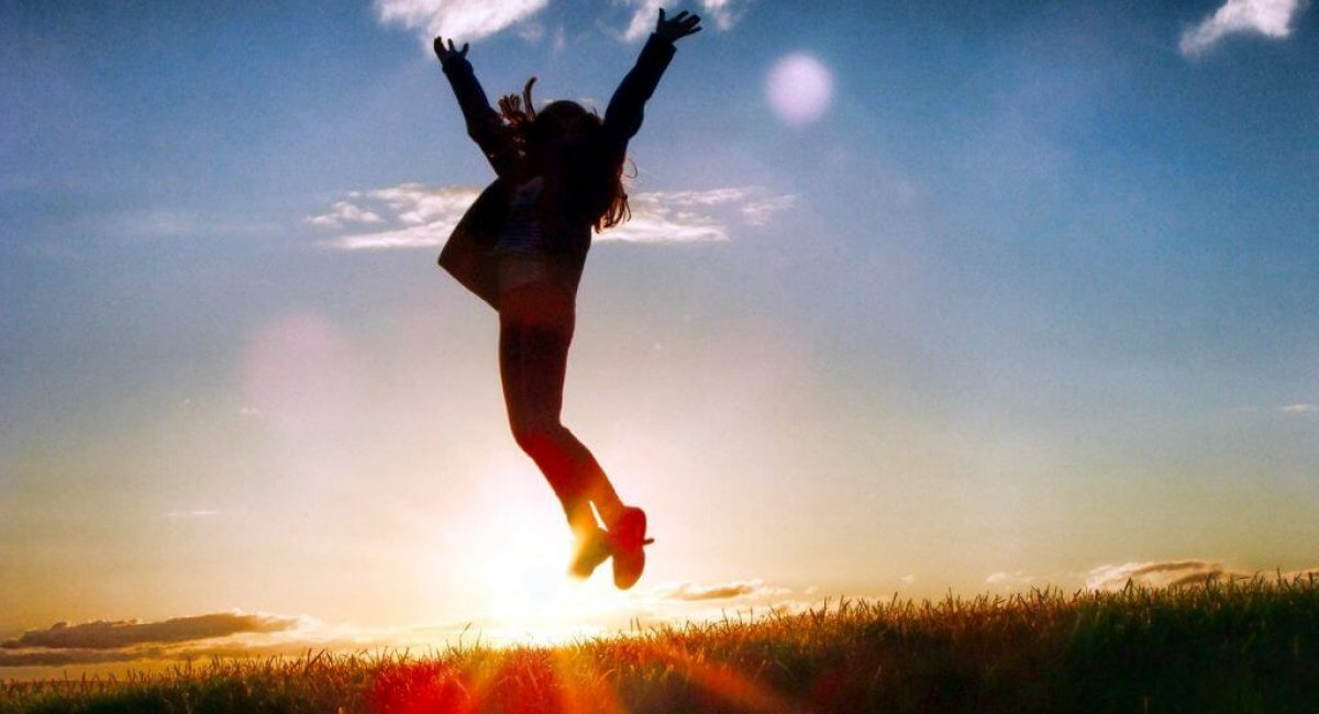 Silhouette of a young woman jumping for joy in a field at sunrise.